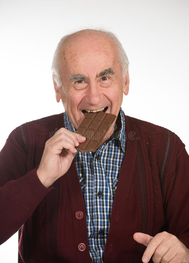 Old man eating chocolate royalty free stock photos