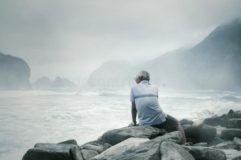 Old man enjoying foggy Papuma beach view. Rear view of old man sitting on the stone while enjoying foggy Papuma beach view at morning time royalty free stock photo