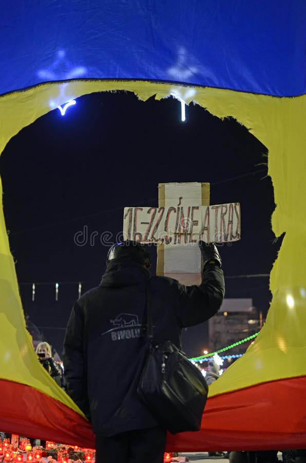 Old man facing crowd. An old man behind a Romanian flag faces a crowd during a commemoration of the Romanian Revolution from 1989