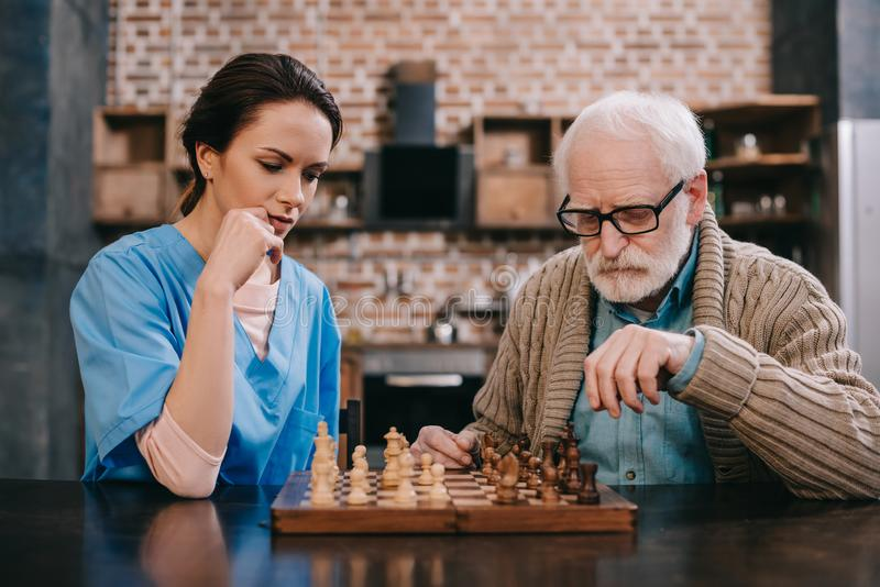 Old man and female caregiver. Playing chess royalty free stock photography