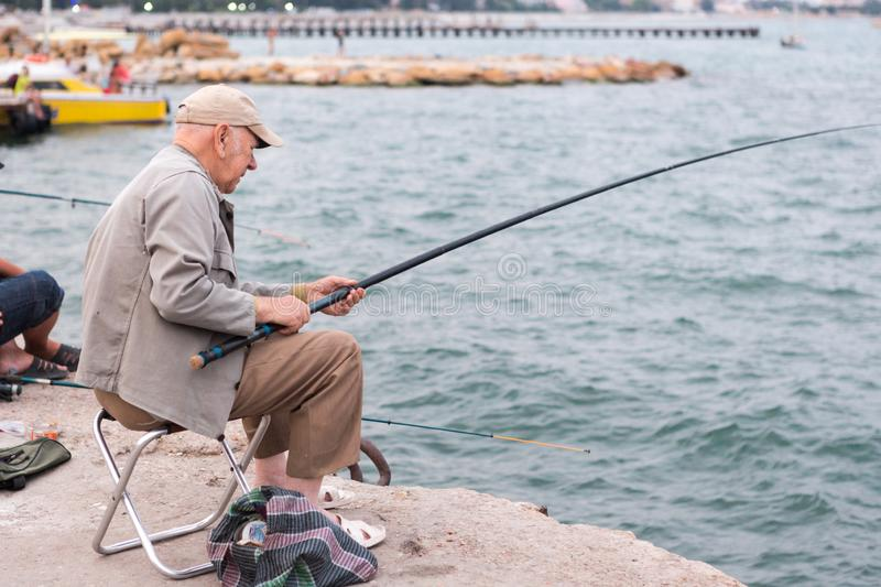 Old man fishing on a fishing rod in the sea, in the evening royalty free stock photography