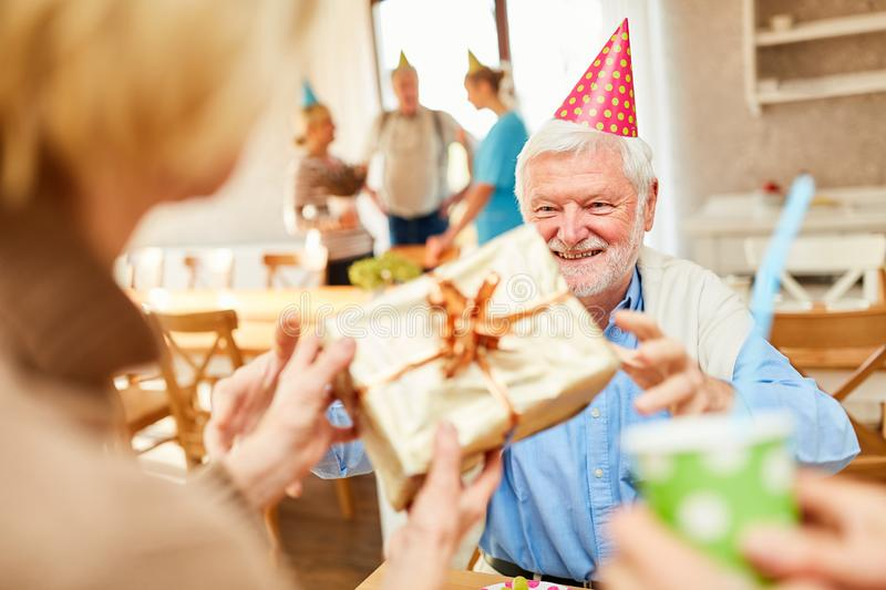 Old man gets gift from friends stock photography