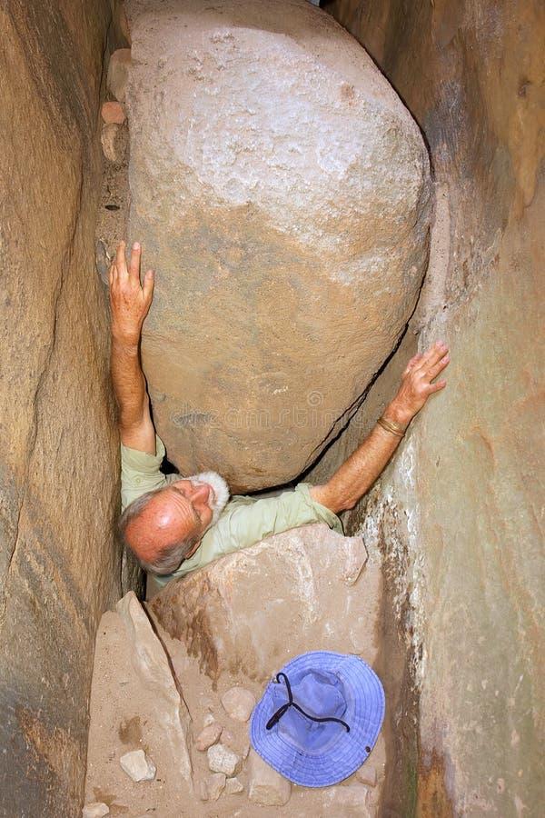 Old man gets stuck between rocks stock photo