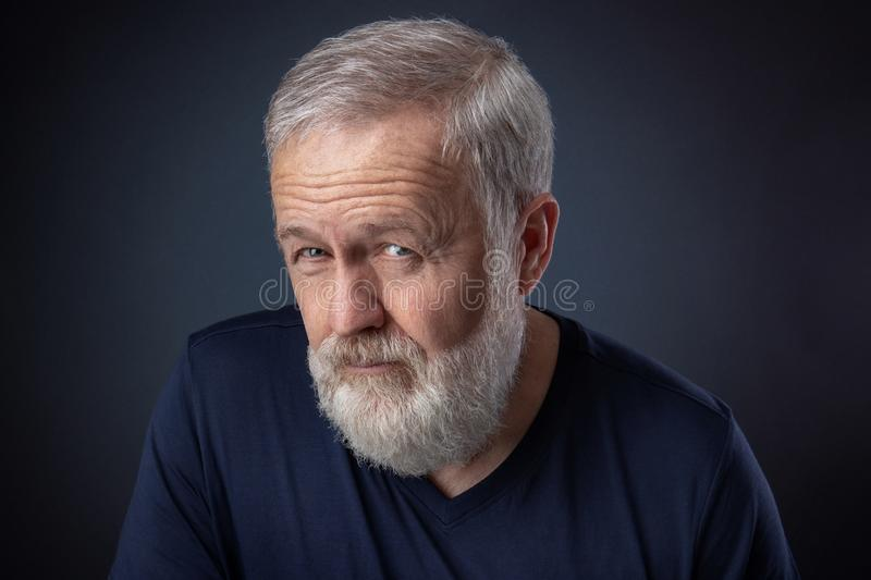 Old man with gray beard looking suspicious stock images