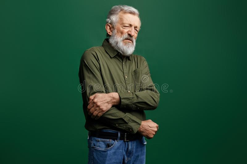 Old man in green T-shirt and jeans with closed eyes holding his elbow in pain royalty free stock image