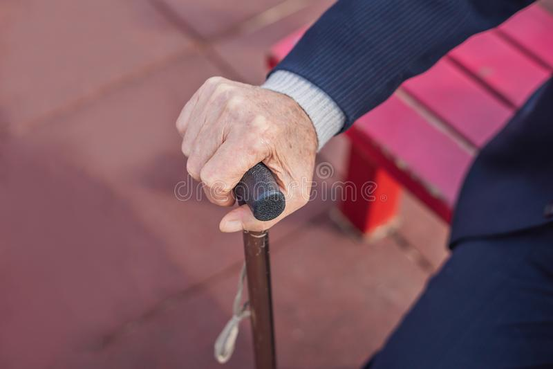 Old man hand holding walking stick outdoor.  royalty free stock photo