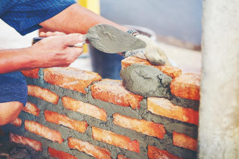 Old man Hand white-wash cement built wall brick new house, Brick stock photography