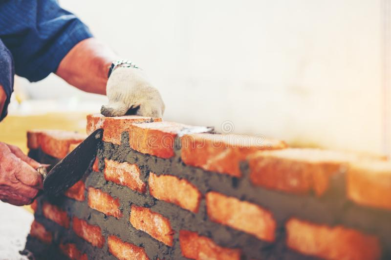 Old man Hand white-wash cement built wall brick new house, Brick. Layer worker installing brick masonry on exterior wall with trowel putty knife local county in stock photography