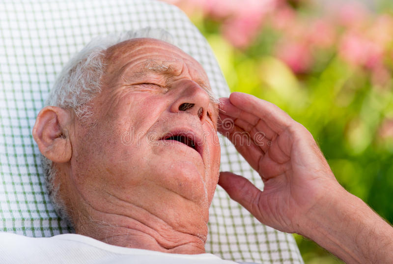 Old man having headache in garden. Old man lying in easy chair in garden and holding hand on forehead because of pain stock photography