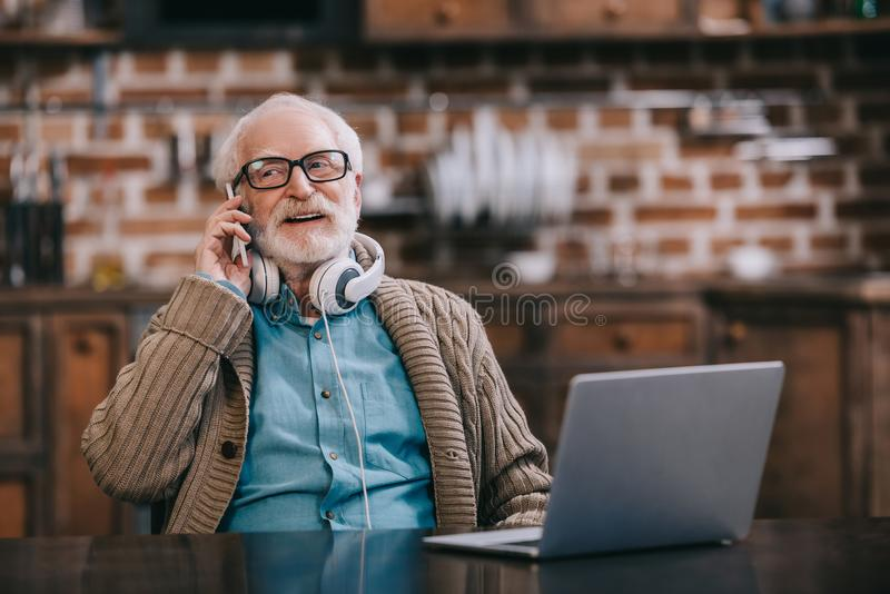 Old man in headphones talking on phone royalty free stock image