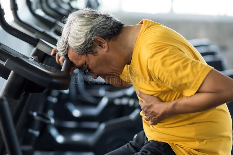 Old man heart attack in fitness gym stock photos