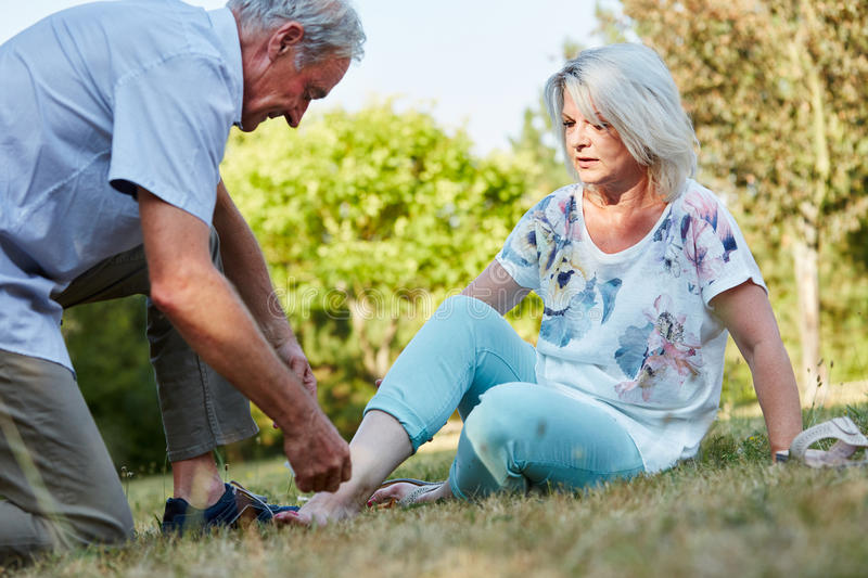 Old man helps woman with sprained ankle stock photography