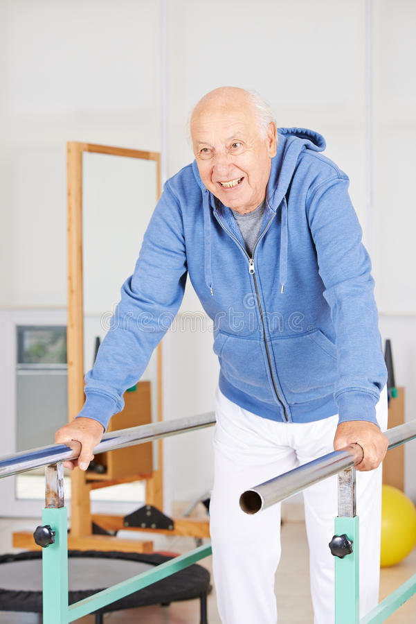 Old man on high bar. Old man standing on high bar in physiotherapy royalty free stock photo