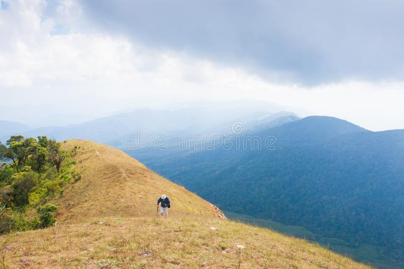 Old man hiker on a top of mountain. Clouds and blue mountains ba stock image