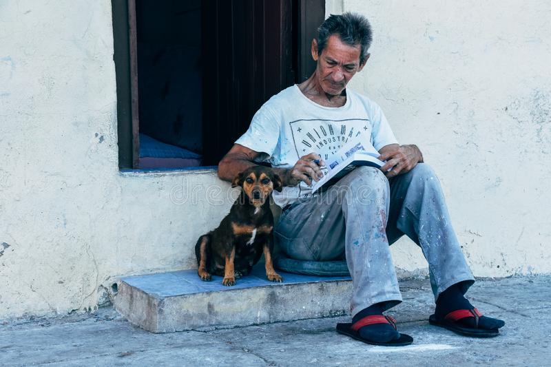A old man with his best friend in Havana city, Cuba. A old man with his best friend sitting on a step in Havana city, Cuba royalty free stock images
