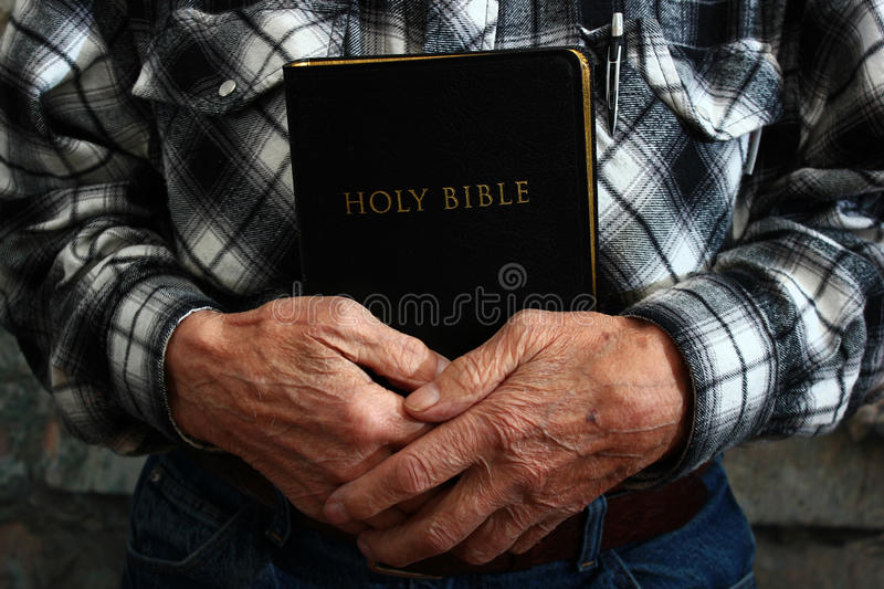 Old Man Holding a Bible. In his hands stock photo
