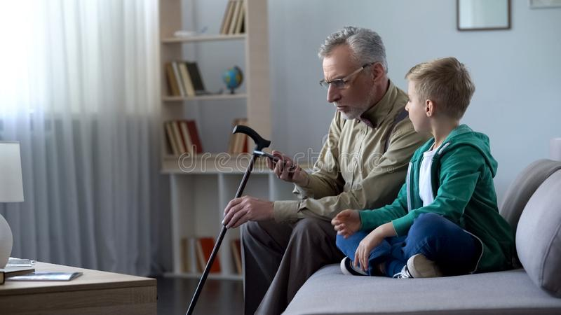 Old man holding cellphone, boy helping him to acquaintance with new technologies stock images