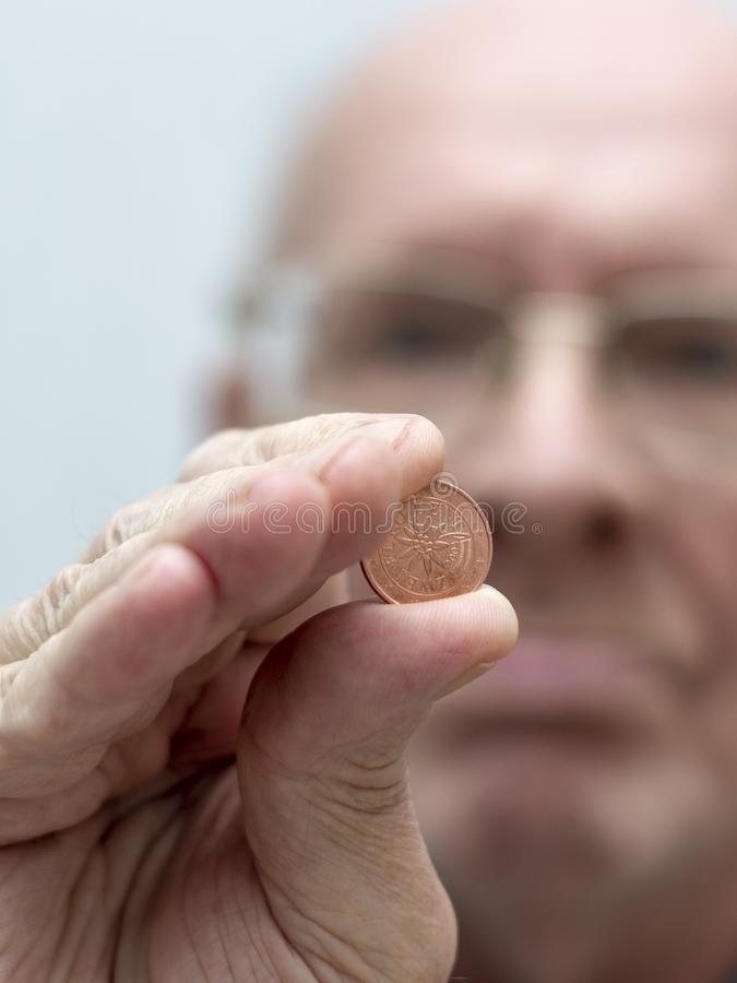 An old man holds in his hand a coin of two euro cent royalty free stock image
