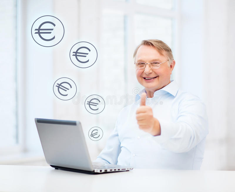 Old man with laptop computer showing thumbs up. Technology, oldness and lifestyle concept - old man in eyeglasses with laptop computer at home showing thumbs up royalty free stock photo