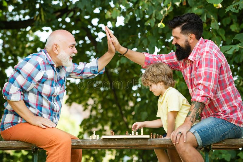 Old man with little boy playing chess. Cute little boy playing chess with Parents. Grandfather and father playing chess royalty free stock images