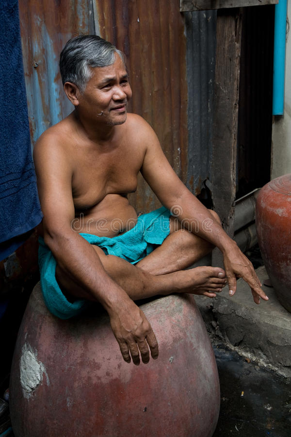 A old man living in a slum stock image