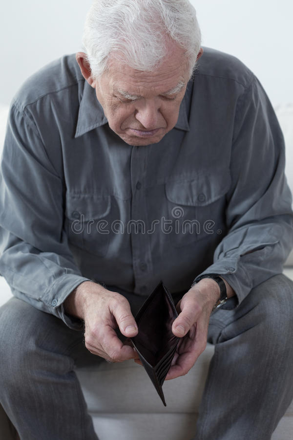 Old man looking at an empty wallet royalty free stock image