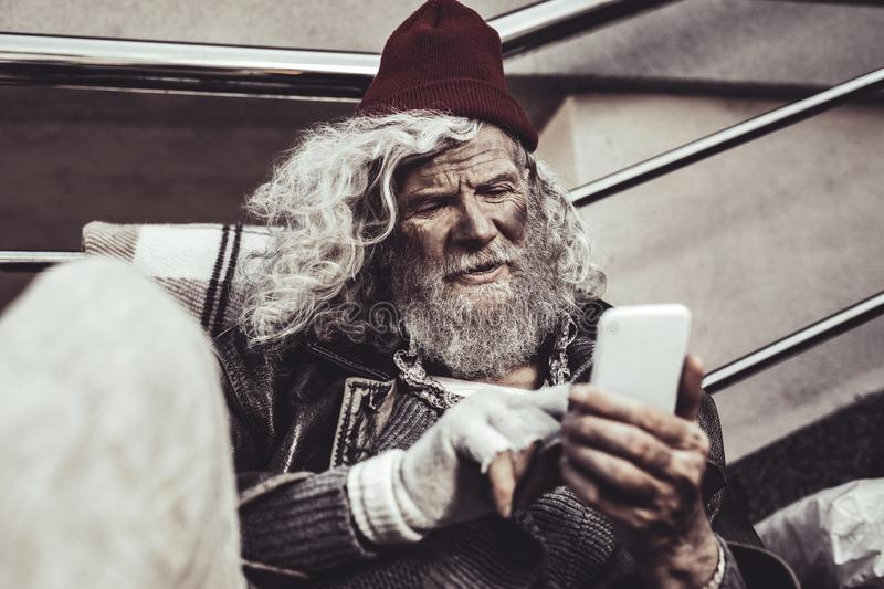 Old man looking like homeless watching on photos of his family on screen. Familiar faces. Frowned old man sitting on the street and looking like homeless royalty free stock photo