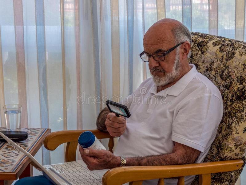 Old man  with magnifying glass reading on the jar with vitamines. Laptop on the knees royalty free stock photography