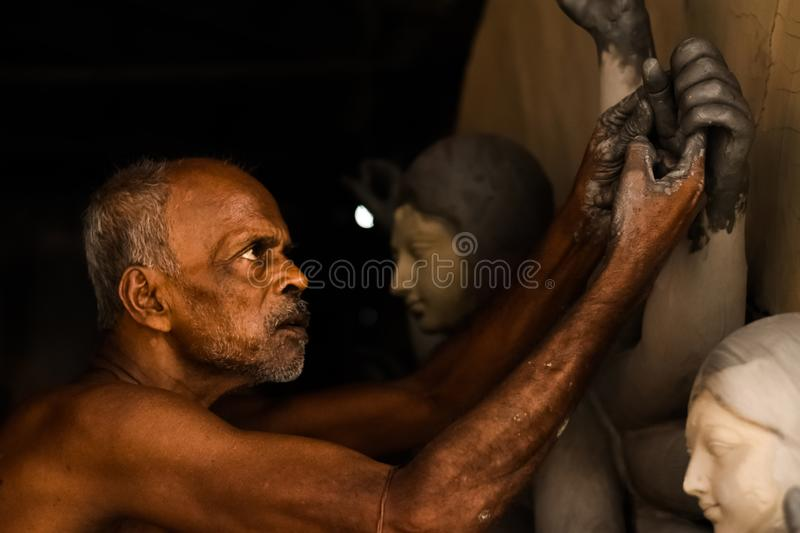 Old man making durga pratima or durga idol worshiped all over the west bengal and also all over the india in autumn season royalty free stock photo