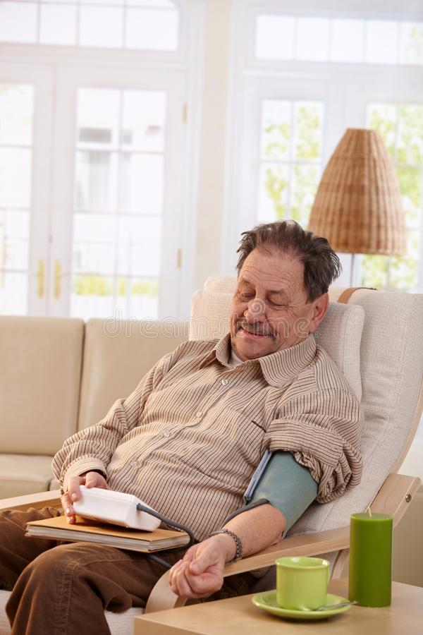 Old Man Measuring Blood Pressure At Home Stock Photo