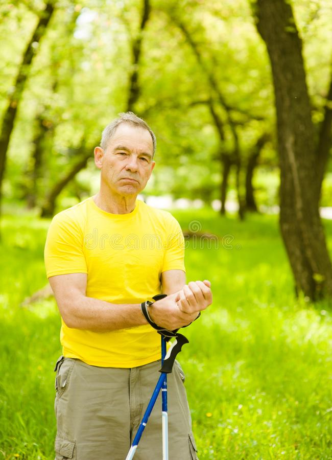 Old man measuring heart rate after nordic walking in the park.  stock images