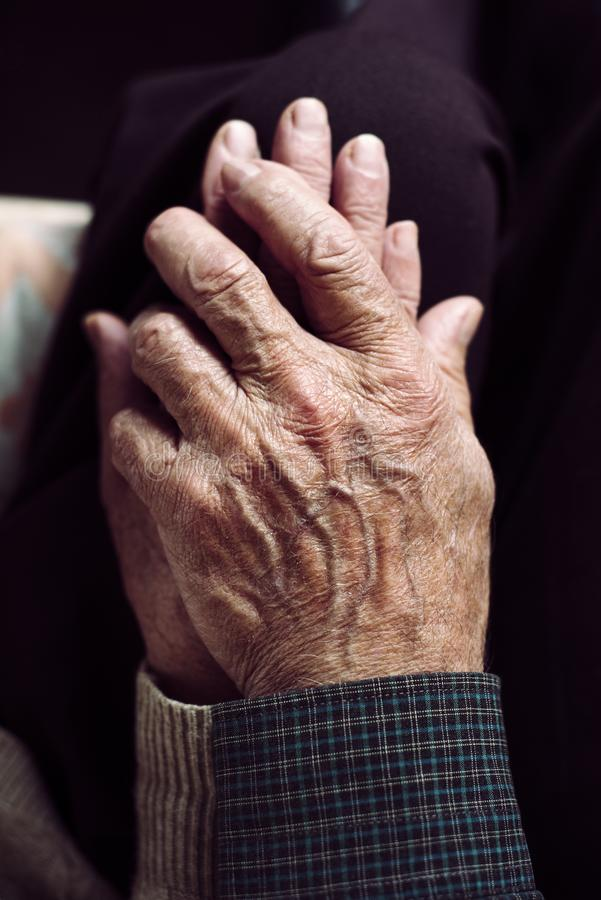 Old man and old woman holding hands. High angle view of an old caucasian man and an old caucasian woman sitting in a couch holding hands with affection royalty free stock photo