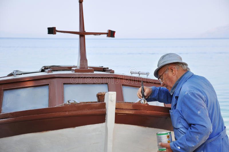 Old man painting boat royalty free stock image