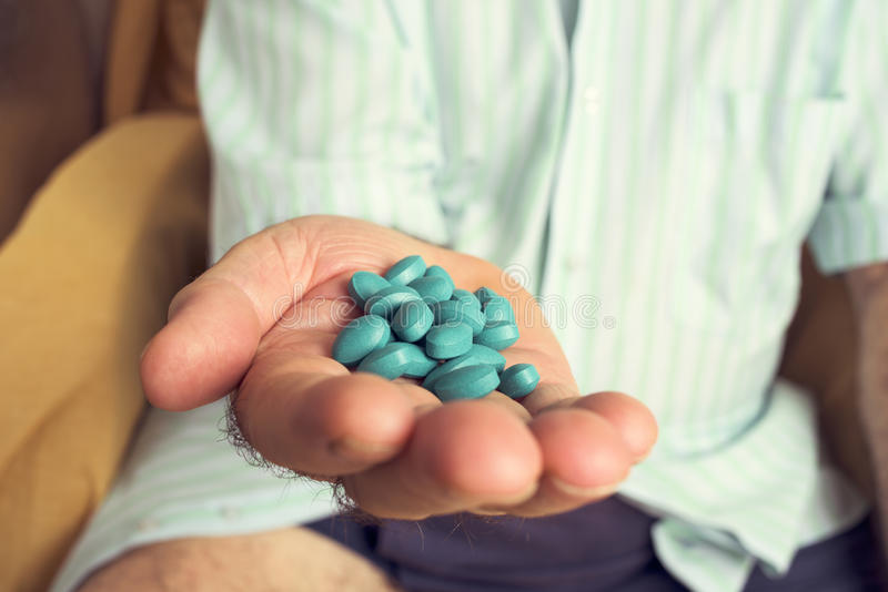 Old man with a pile of blue pills in his hand stock photo