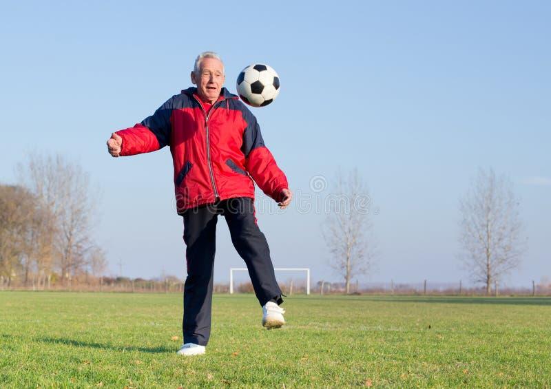 Old man playing football royalty free stock image