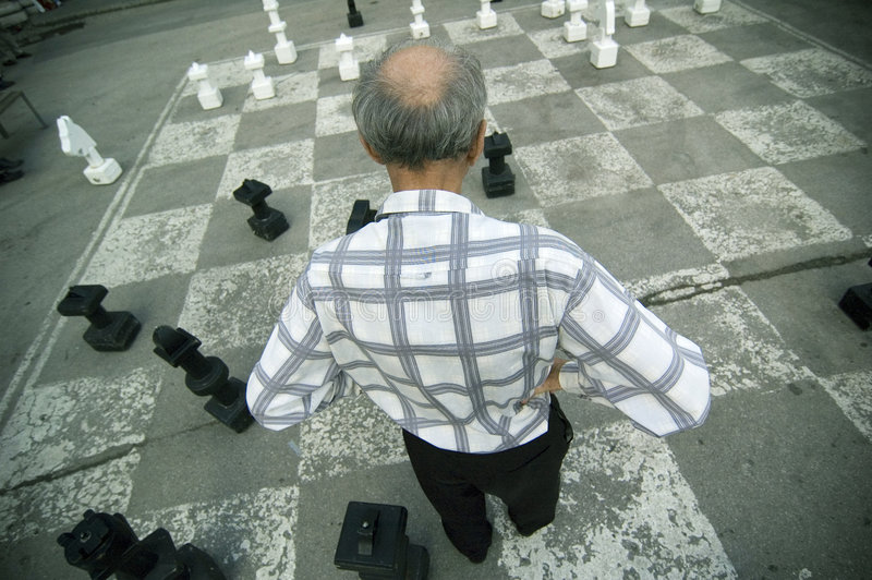 Old Man Playing Oversize Chess Board stock image