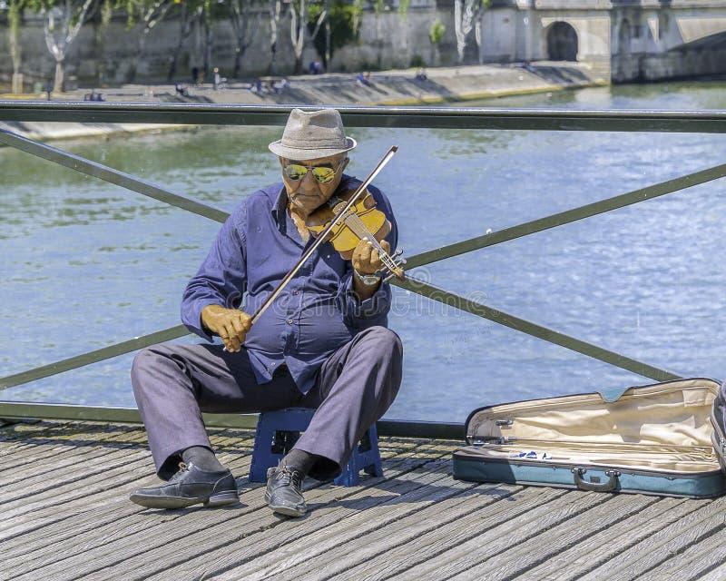 Old man playing violin at Pont des Arts - The Love Lock Bridge. Paris, France - July 4, 2017: Old man on a stool playing violin for tips on Pont des Arts stock photos