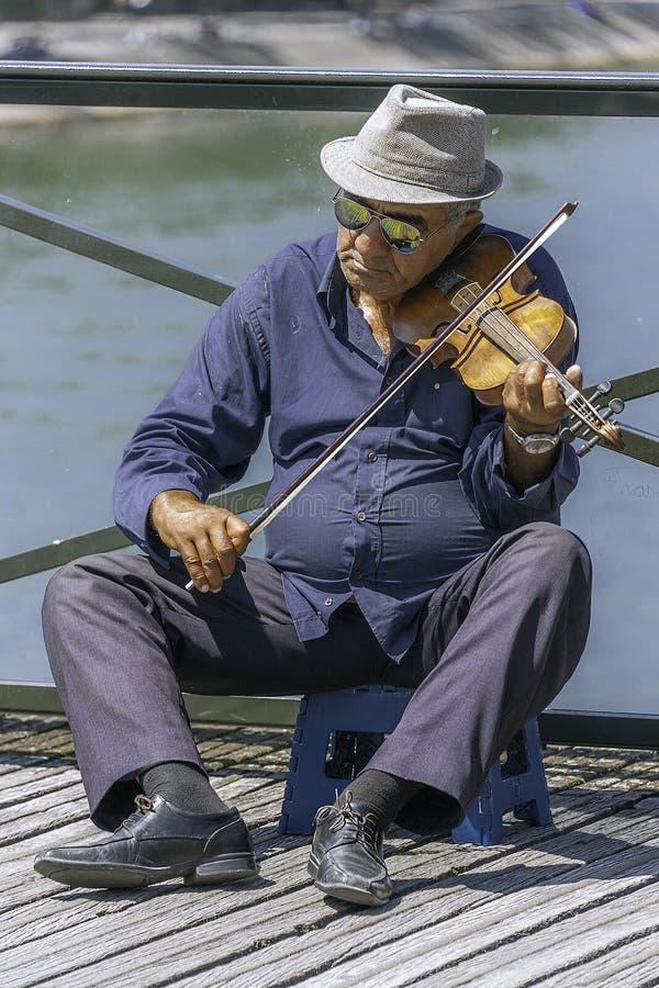 Old man playing violin at Pont des Arts - The Love Lock Bridge. Paris, France - July 4, 2017: Old man on a stool playing violin for tips on Pont des Arts royalty free stock images
