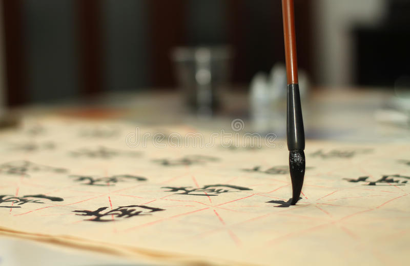 Old man practicing callingraphy using a brush pen royalty free stock photography