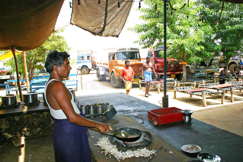 Old man preparing food on the roadside eatery place in the middle of highways, Kerala. Indian truck drivers stops there vehicles and have their food royalty free stock image