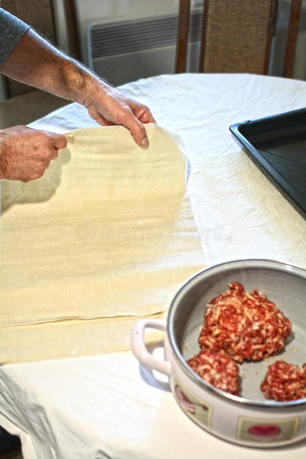 An old man preparing a traditional Mediterranean meat pie royalty free stock photos