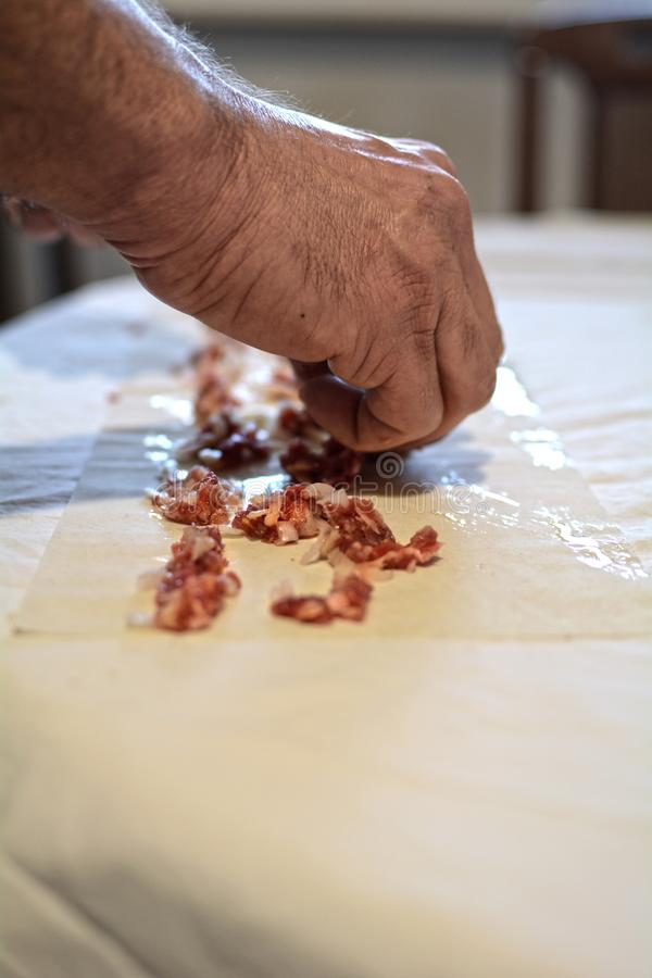 An old man preparing a traditional Mediterranean meat pie royalty free stock photography