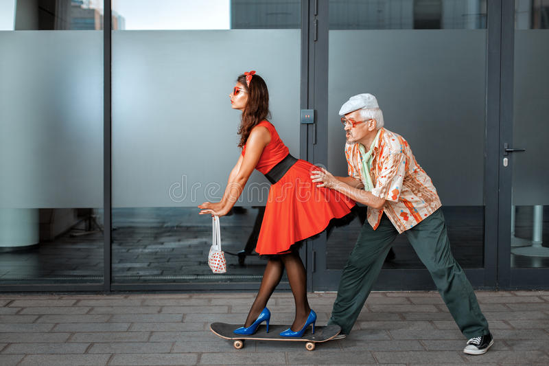 Old man pushes a woman. stock photography