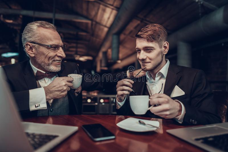 Old Man put hand on shoulder of Young Businessman stock photo