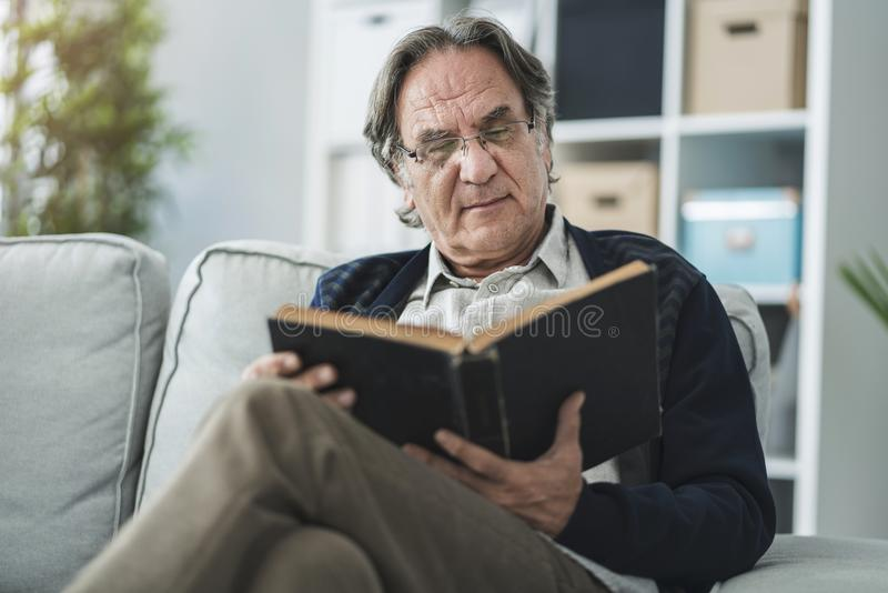Old man reading book at home royalty free stock images