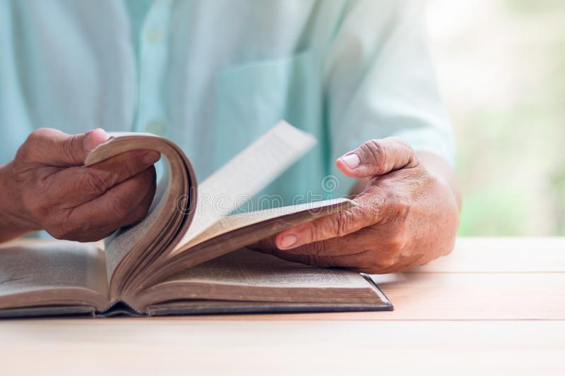Old man reading book on light brown wooden table surface, flipping movement stock photography