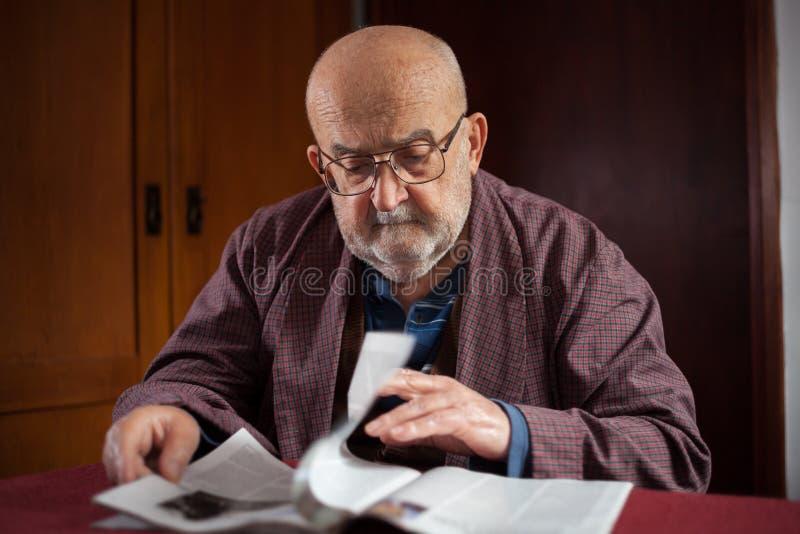Old man reading magazine stock photos