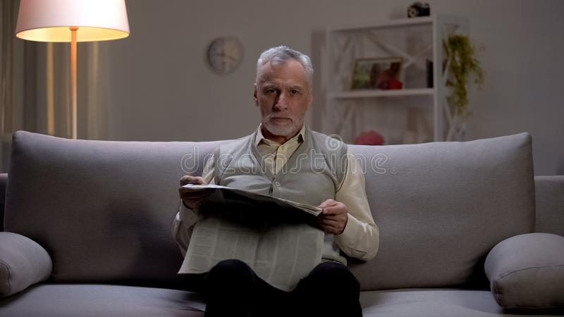 Old man reading newspaper in evening, seriously looking into camera, bad news stock photo