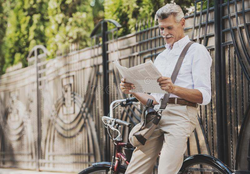 Old man Reading Newspaper near Bicycle in Park. royalty free stock images