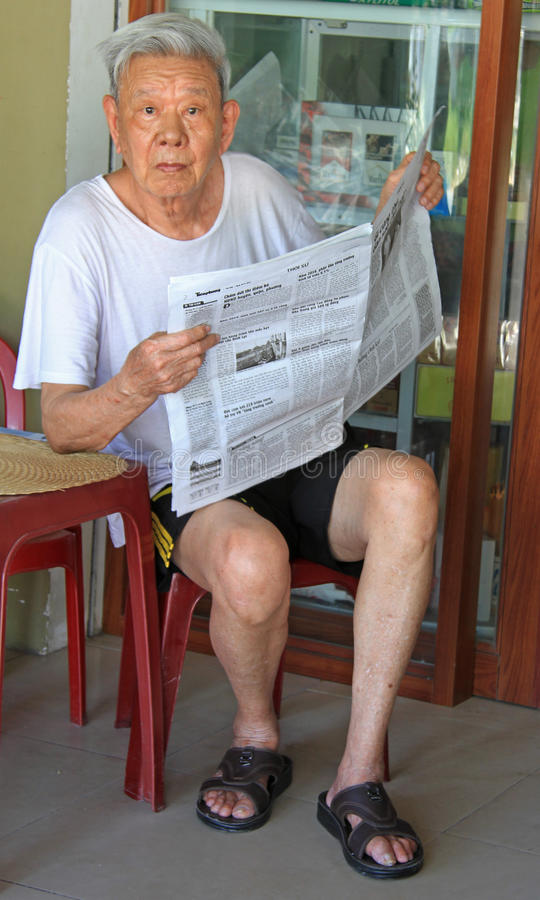 Old man is reading newspapers outdoor in Vinh, Vietnam stock image